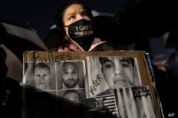 A demonstrator carries a sign bearing images of former Minneapolis police Officer Derek Chauvin and others, during a protest...