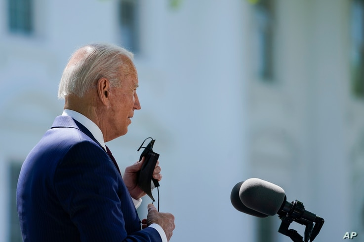 President Joe Biden removes his face mask to speak about COVID-19, on the North Lawn of the White House, Tuesday, April 27,…