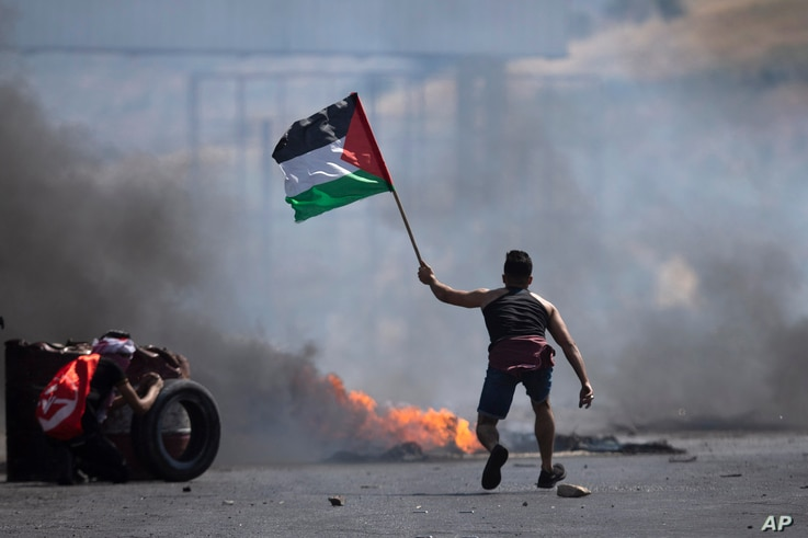 A protester waves the Palestinian flag during clashes with the Israeli forces at the Hawara checkpoint, south of the West Bank…