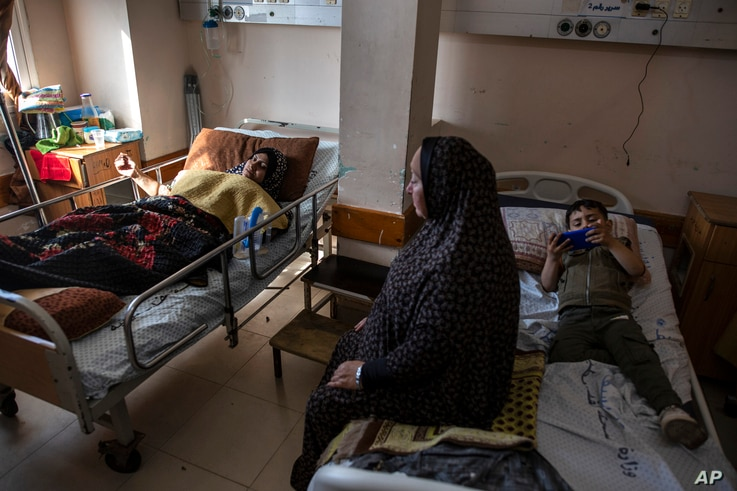 Ihsan Al-Masri, 24, left, rests at the Shifa hospital in Gaza City, May 13, 2021, as her son plays on a mobile phone on the bed…