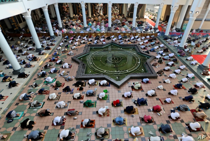 Muslims pray at a distance from one another to prevent the spread of the coronavirus outbreak during an Eid al-Fitr prayer at the end of ...