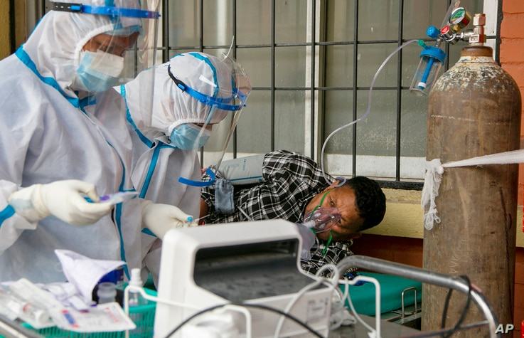 Nepalese paramedics treat a COVID-19 patient outside an emergency ward of a government run hospital in Kathmandu, Nepal, Friday...