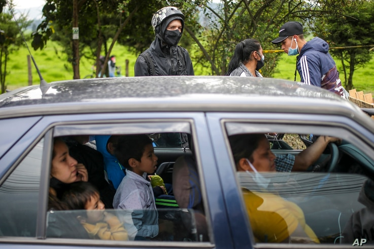 A family sits in their car at a roadblock set up by anti-government protesters in Madrid, on the outskirts of Bogota, Colombia,...