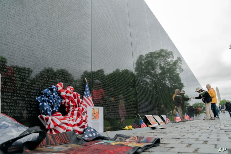 A visitors reads the names of the fallen soldiers at Vietnam Veterans Memorial at the National Mall ahead of Memorial Day, in...