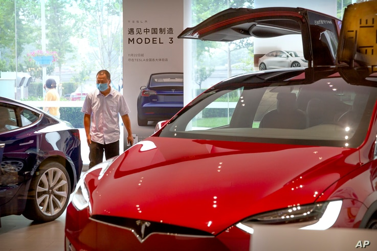 A customer wearing a face mask to protect against the new coronavirus looks at automobiles in a Tesla car showroom in Beijing,…