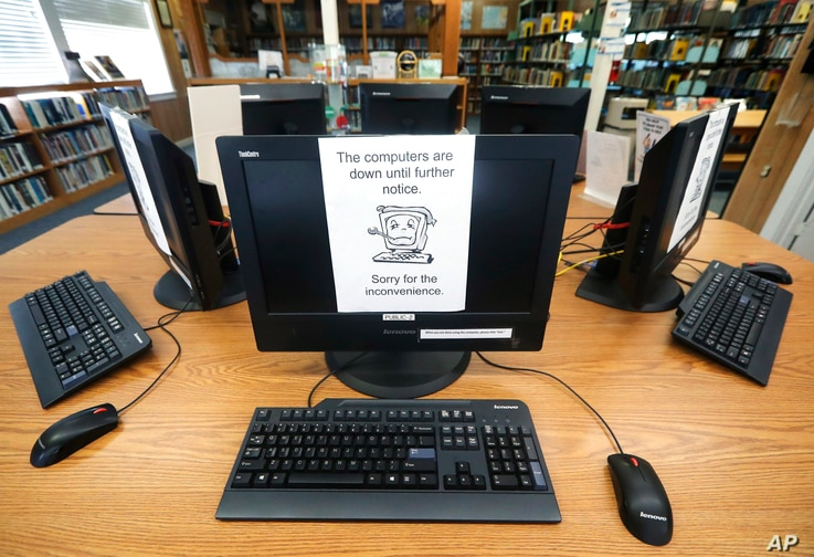 FILE - In this Aug. 22, 2019, file photo, signs on a bank of computers tell visitors that the machines are not working at the…