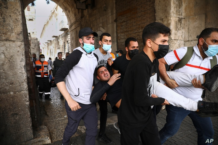 Palestinians evacuate a wounded protester during clashes with Israeli security forces at the Lions Gate in Jerusalem's Old City…