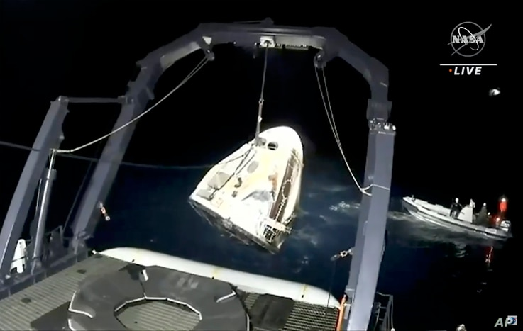 In this image made from NASA TV video, the SpaceX Dragon capsule is retrieved from the Gulf of Mexico near the Florida…
