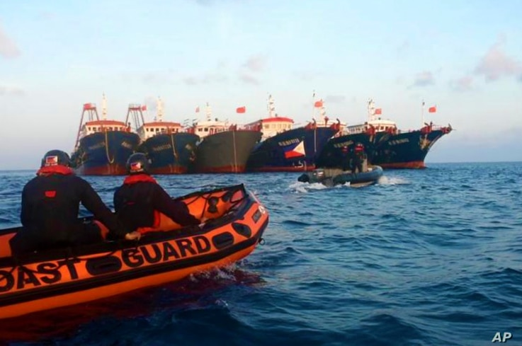 In this handout photo provided by the Philippine Coast Guard, members of the Philippine Coast Guard use rubber boats as they...