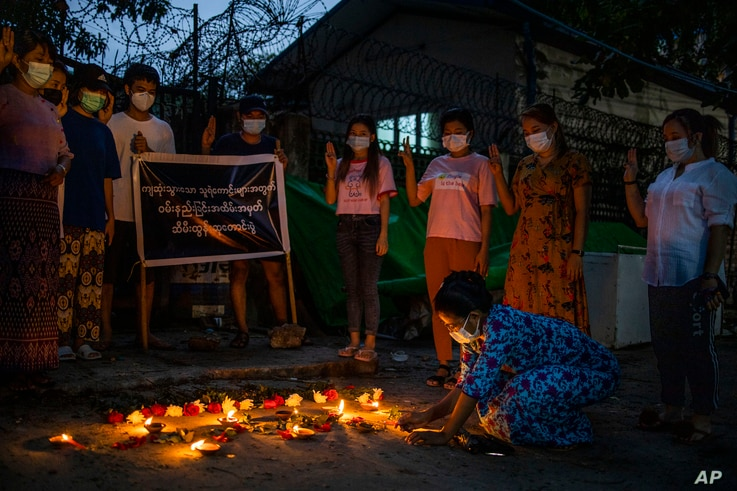 A woman lights a candle while others flash the three-fingered sign of resistance during a candlelight vigil to remember those…