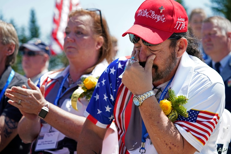 John Biernacki of Greenville, Tex., wipes tears during the unveiling of a monument to honor the military passengers of Flying…
