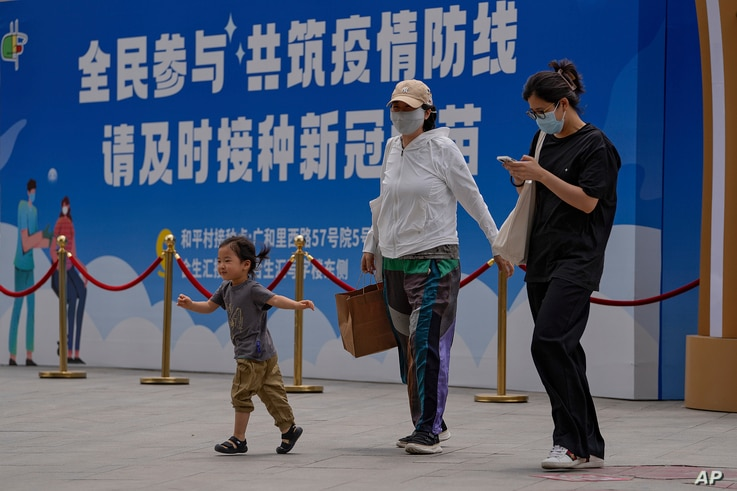 Women wearing face masks to help curb the spread of the coronavirus and a child walk by a billboard showing the words 'All...