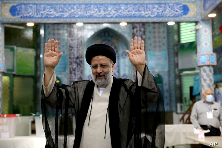 Ebrahim Raisi, a candidate in Iran's presidential elections, raises his hands as he casts his vote at a polling station in...