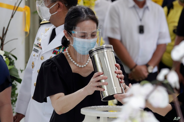 Ballsy Aquino-Cruz holds the urn of her brother former Philippine President Benigno Aquino III before he is placed on the tomb...