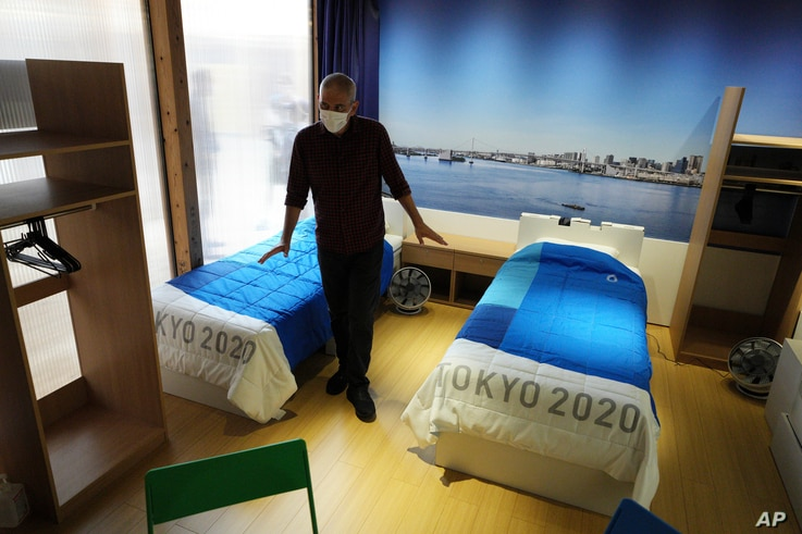 A journalist looks at cardboard beds, for the Tokyo 2020 Olympic and Paralympic Villages, which are shown in a display room the...