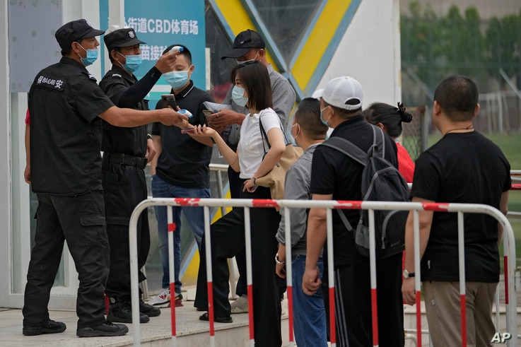 Security guards help masked residents to scan their health code as they line up to receive the Sinopharm COVID-19 vaccine at…