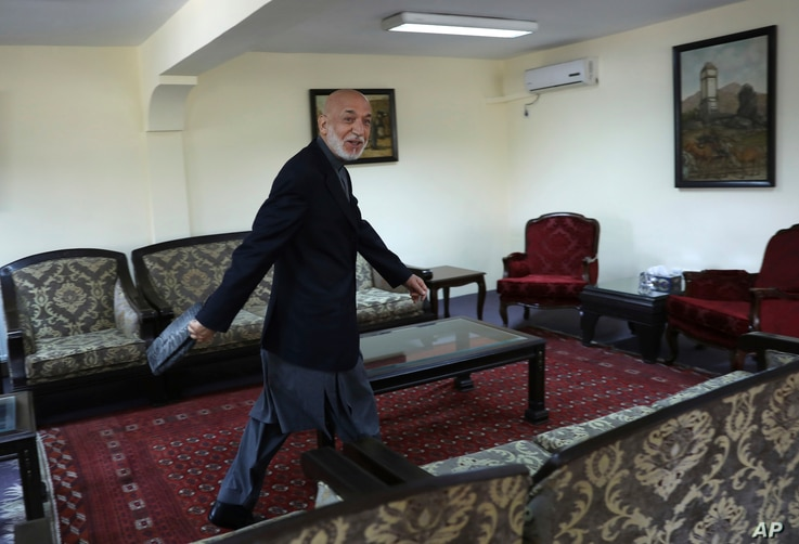 Former Afghan President Hamid Karzai leaves after an interview with the Associated Press at his house, in Kabul, Afghanistan,...
