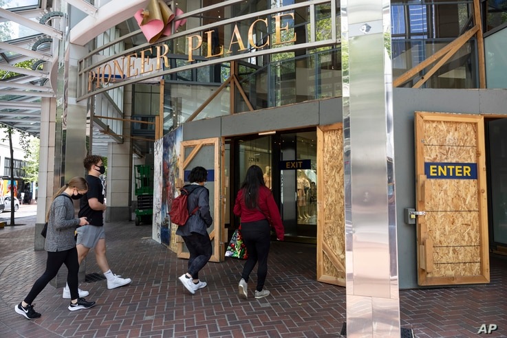 Shoppers walk into Pioneer Place shopping mall still protected by wooden panels to prevent windows being smashed by on-going…