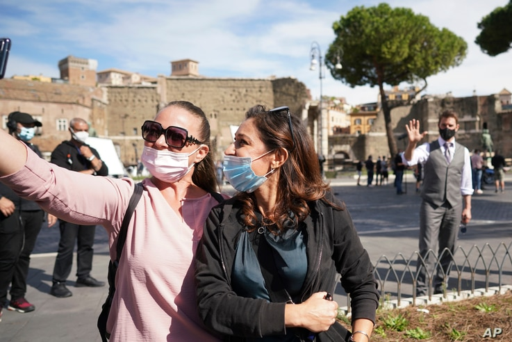 Two women wear a face mask to prevent the spread of COVID-19 as they take a selfie with actor Tom Cruise in the background…