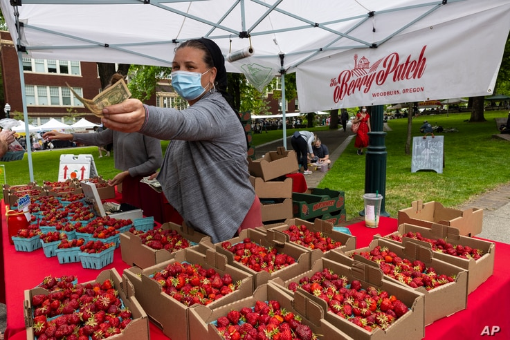 Nancy Sharabarin hands money to a customer buying strawberries at the Saturday farmers market as business opens up with a…