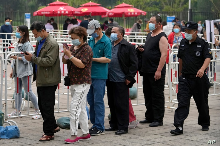 A security guard watches residents wearing face masks to help curb the spread of the coronavirus line up to receive the…