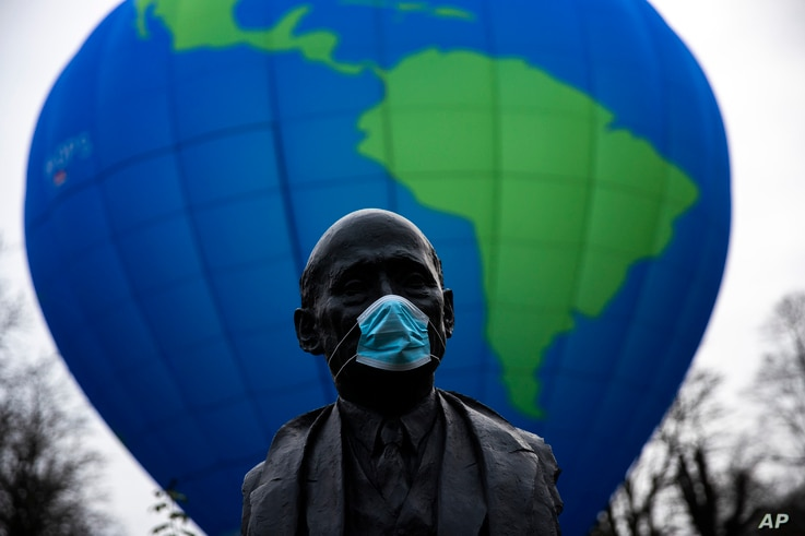 The bust of French statesman Robert Schuman, one of the founders of the European Union, is seen while environmental activists…