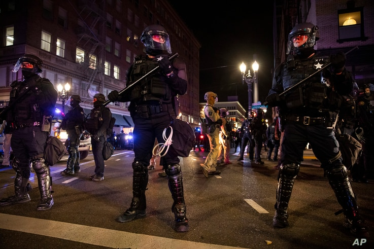 FILE - In this Nov. 4, 2020, file photo, police form a perimeter during protests following the Nov. 3 presidential election in…