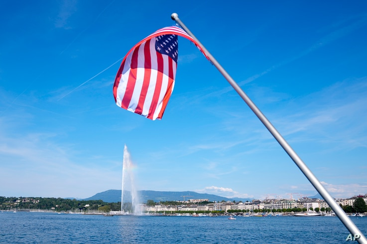 The United States flag waves on a bridge near the fountain Jet d'eau in the Lake Geneva in Geneva, Switzerland, Tuesday, June...