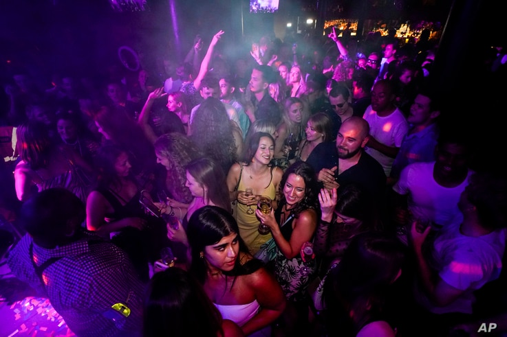 People drink on the dance floor shortly after the reopening, at The Piano Works in Farringdon, in London, Monday, July 19, 2021...