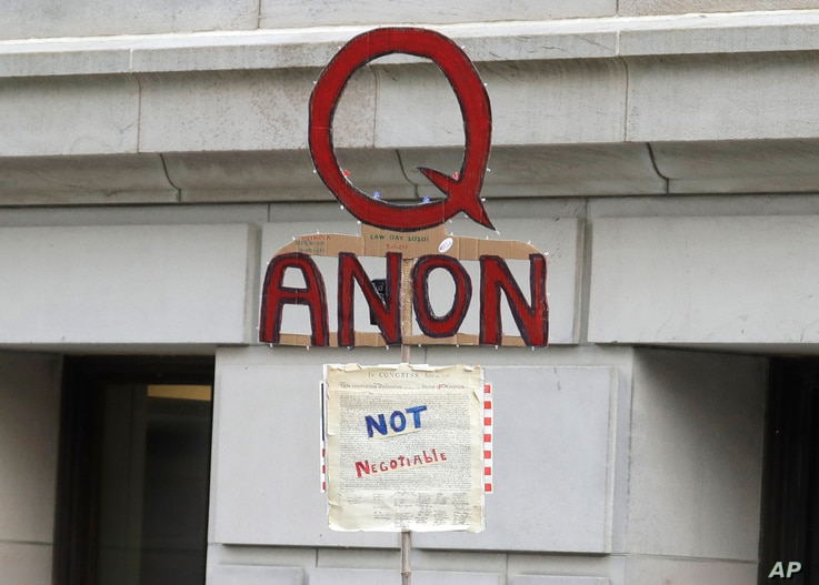 In this May 14, 2020, photo, a person carries a sign supporting QAnon at a protest rally in Olympia, Wash., against Gov. Jay…