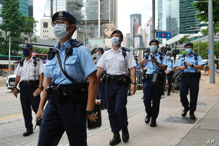 Police officers patrol outside a court Friday, July 30, 2021, as they wait for Tong Ying-kit to leave the court in Hong Kong...