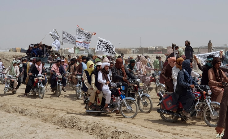 Supporters of the Taliban carry the Taliban's signature white flags in the Afghan-Pakistan border town of Chaman, Pakistan,…