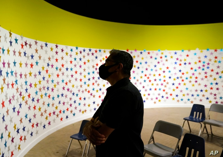The secretary of the Department of Health and Social Services Xavier Becerra, looks at a wall of stars, one for each child ...