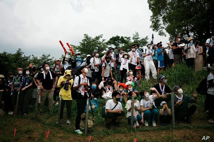 Masked fans watch from a hillside during the men's cross country mountain bike competition at the 2020 Summer Olympics, Monday,...
