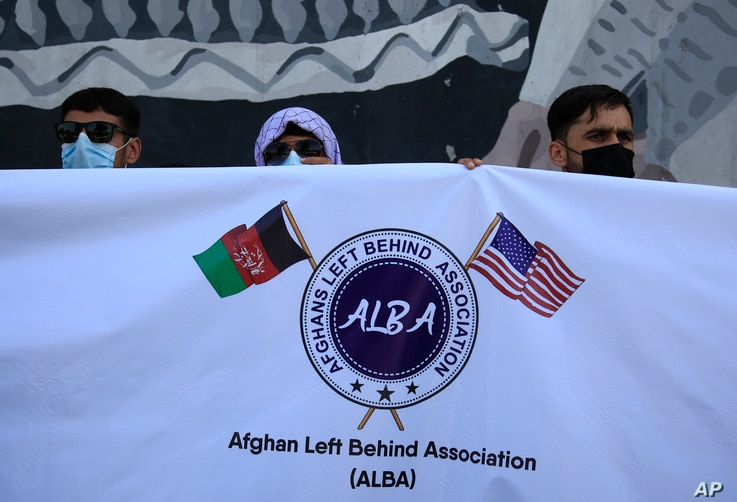 Former Afghan interpreters hold placards during a demonstrations against the US government, in front of the US Embassy in Kabul…