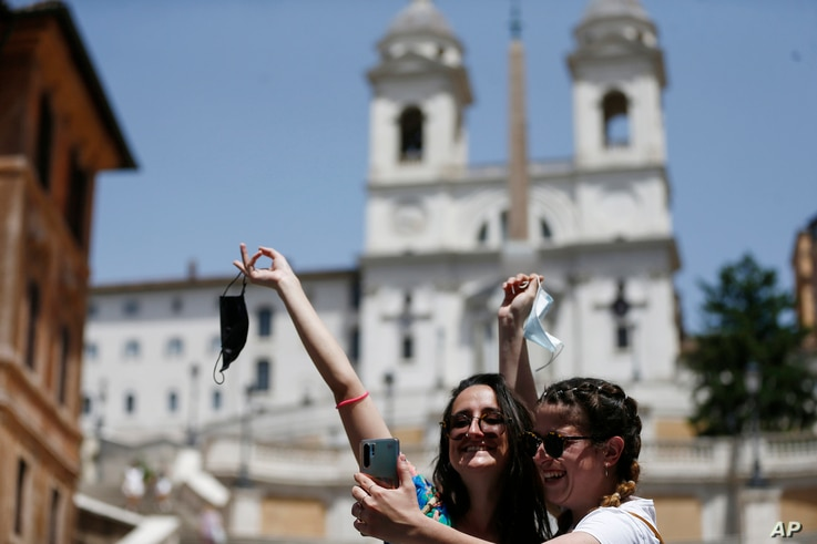 Two women take a selfie at the Spanish Steps in Rome, Monday, June 28, 2021. Italians took off their face masks and breathed a…