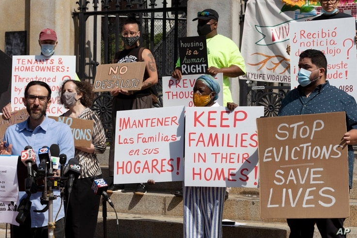 People from a coalition of housing justice groups hold signs protesting evictions during a news conference outside the…