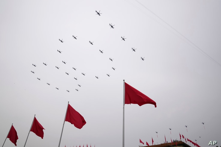 """Helicopters fly over Chinese flags at Tiananmen Square in the formation of """"100"""" during a ceremony to mark the 100th…"""