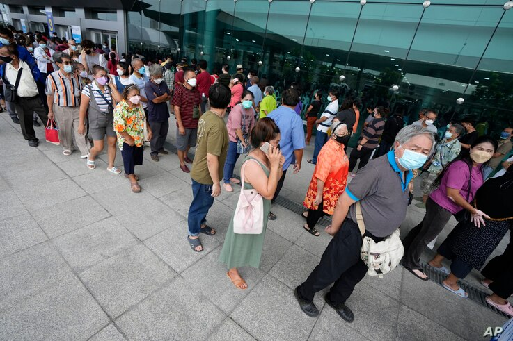 Residents wait on line to receive shots of the AstraZeneca COVID-19 vaccine at the Central Vaccination Center in Bangkok,...