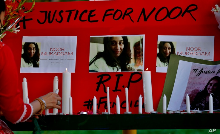 A women's rights activist places a candle beside a poster with the pictures of Noor Mukadam, who was recently beheaded, during...