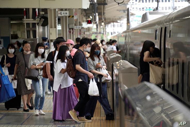Passengers wearing face masks to help curb the spread of the coronavirus get on board a west-bound bullet train at Tokyo...