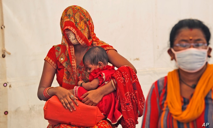 Women wait to receive the vaccine for COVID-19 in New Delhi, India, Friday, July 2, 2021. India crosses a grim mark of 400,000…