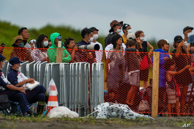 People watch from behind a security fence during the final day of the surfing competition at the 2020 Summer Olympics, Tuesday,...