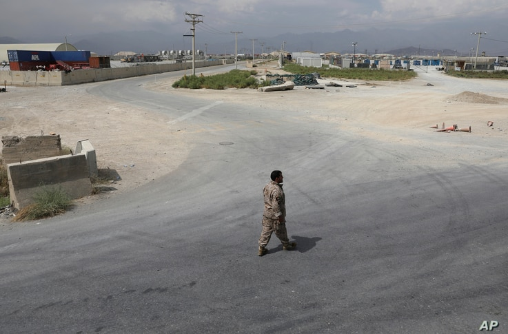 A member of the Afghan security forces walks in the sprawling Bagram air base after the American military departed, in Parwan…