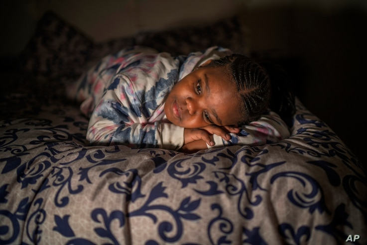 Tshimologo Bonolo, 8, poses for a photograph at her house in Soweto, South Africa, Saturday, June 26, 2021. She lost her father…