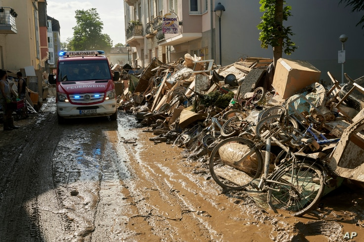 A fire department vehicle drives through a street lined with debris after extreme weather in Bad Neuenahr-Ahrweiler, Germany,…