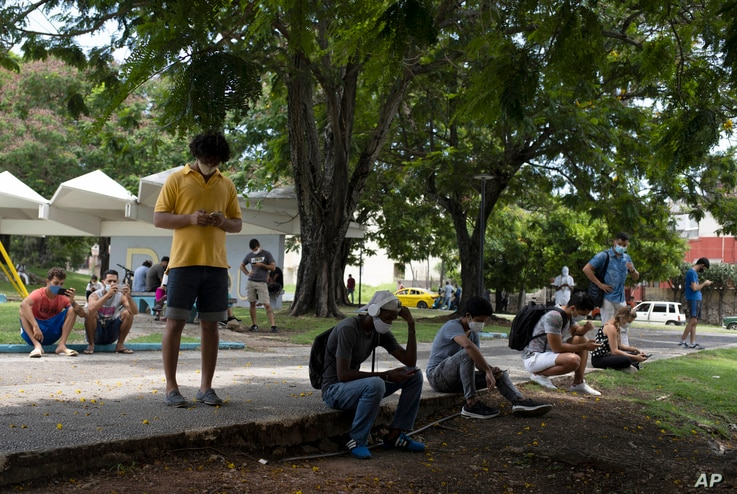 People gather in Martyrs Park where wifi connections are working in Havana, Cuba, Tuesday, July 13, 2021. Cuban President…