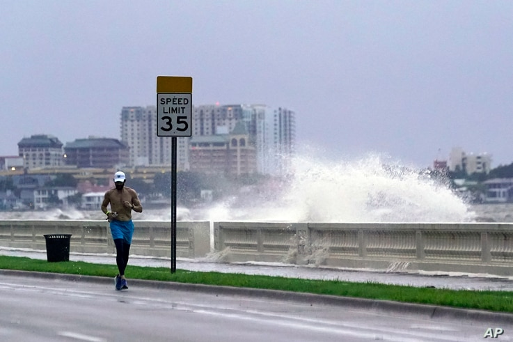 A jogger makes his way along Bayshore Blvd., in Tampa, Fla. as a wave breaks over a seawall, during the aftermath of Tropical...
