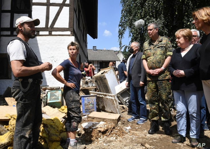 German Chancellor Angela Merkel, 2nd right, and Rhineland-Palatinate State Premier Malu Dreyer, right, talk to residents during…