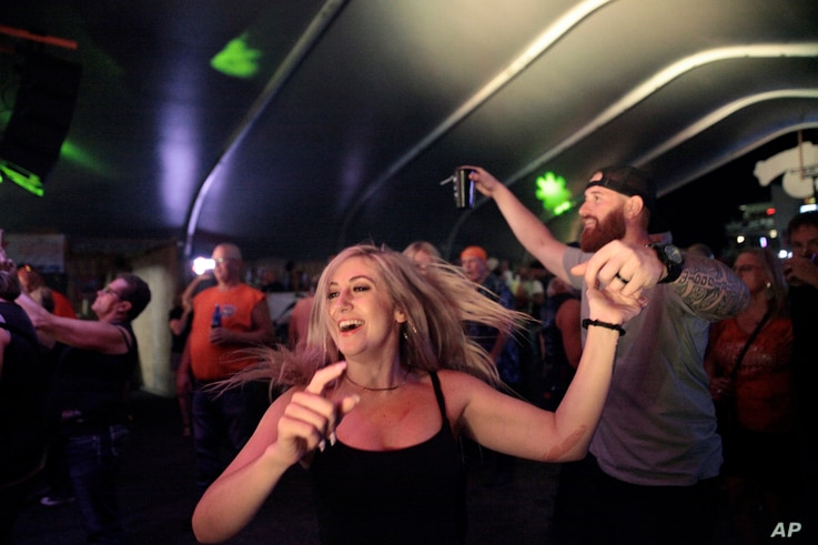Rallygoers dance at a rock show on Thursday, Aug. 5, 2021, in Sturgis, S.D.The Sturgis Motorcycle Rally starts Friday, even as…